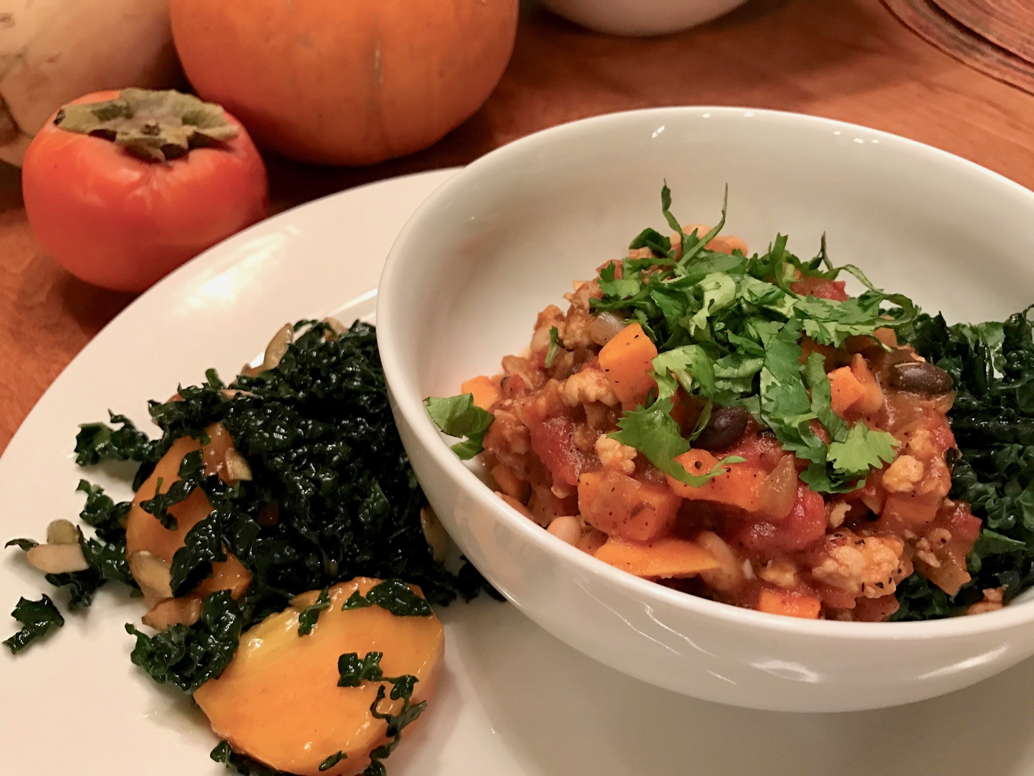 bowl of Turkey, pumpkin and sweet potato chili with a persimmon and kale salad on the side